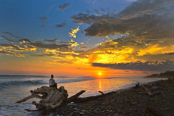 Woman watching sunset over the ocean at Dominical Beach, Costa Rica