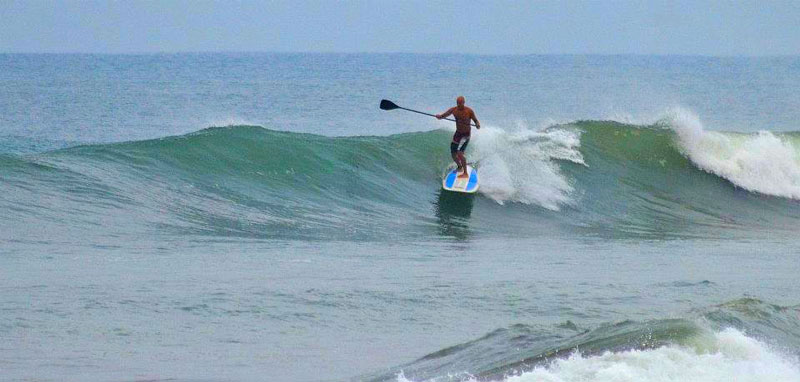 Danyasa Retreat Center owner Brendan Jaffer surfing on a stand up paddle board (SUP)