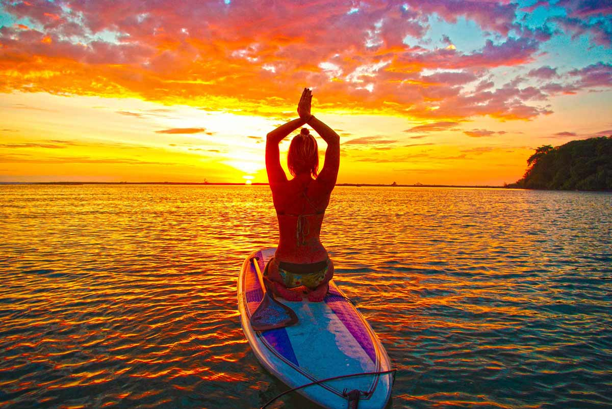 Sofiah doing stand up paddle board (SUP) yoga at sunset in Baru River in Dominical Costa Rica