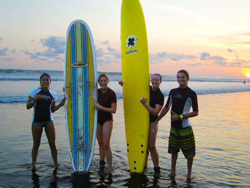 surf instructors and surf students after a lesson at the beach in Dominical Costa Rica
