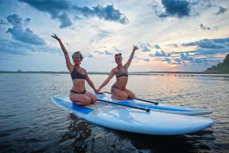 yoga instructors Sofiah and Heidi on SUP boards holding hands and waving in Dominical, Costa Rica