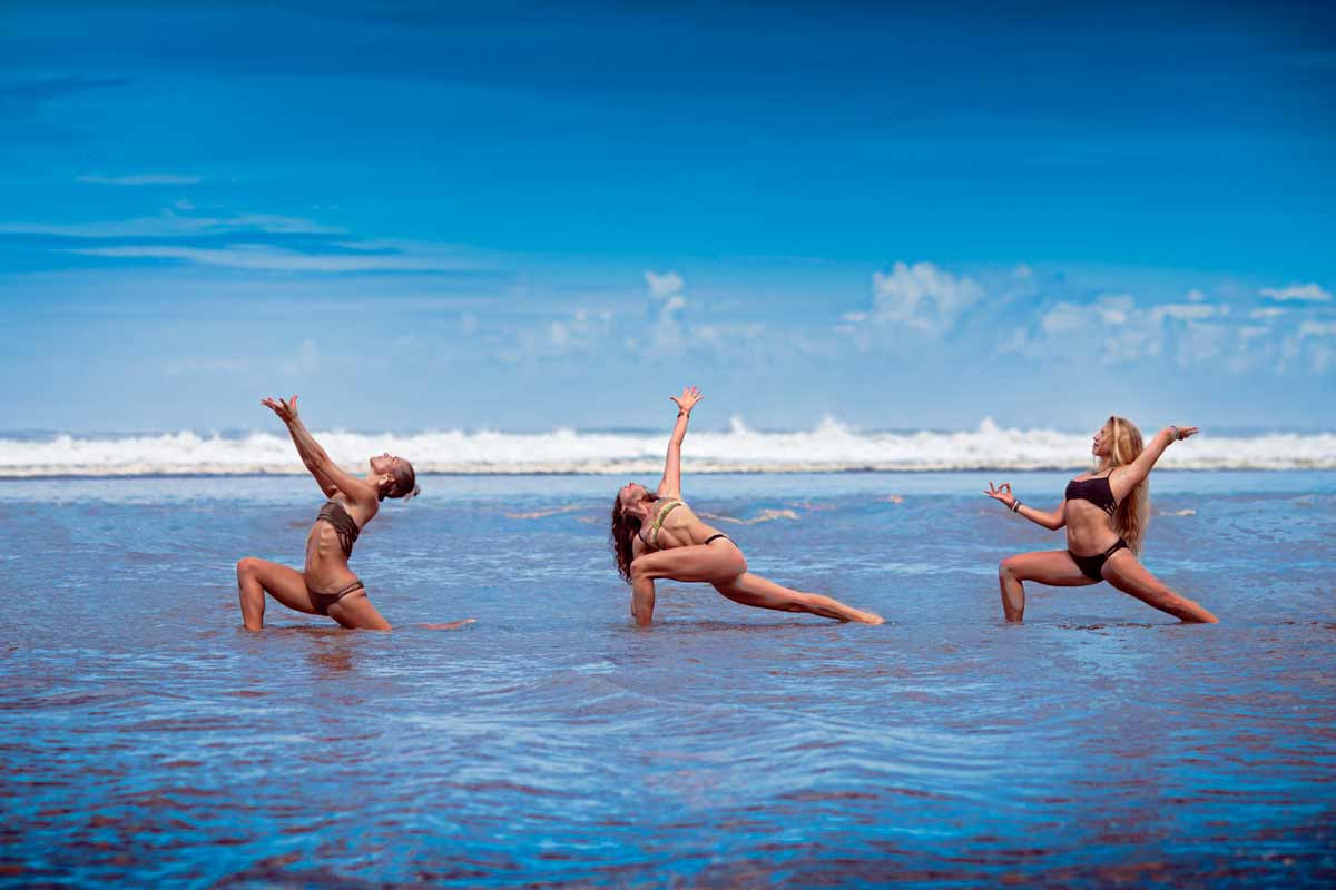 Women doing yoga in the warm ocean in Costa Rica
