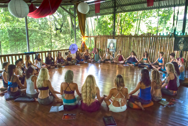 Students from 200 Hour Yoga Teacher Training sitting in Danyasa studio in a circle holding hands